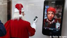 LONDON, ENGLAND - DECEMBER 26: A man looks at a display of a Santa Claus figure with an Iphone at the Apple Store on Regents Street on December 26, 2010 in London, England. Thousands of shoppers seeking a Boxing Day sale bargain are filling Oxford Street and Regent's Street. (Photo by Peter Macdiarmid/Getty Images)