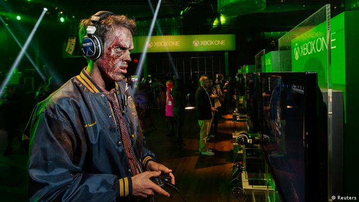 A man dressed as a zombie plays video games on an Xbox One console during a midnight launch event in New York, November 21, 2013. REUTERS