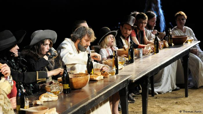 Actors sit at a table in a scene from the play Genesis, Copyright: Thomas Aurin