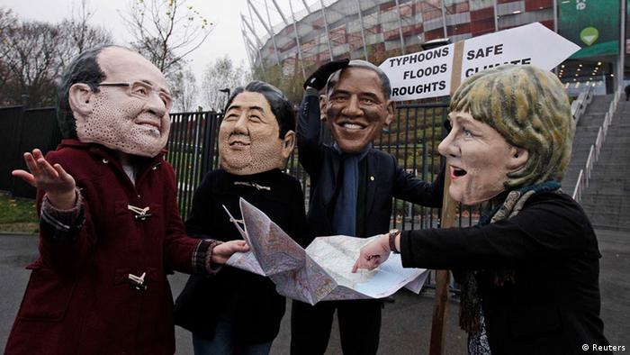 Protesters wearing masks of France's President Francois Hollande (L-R), Japan's Prime Minister Shinzo Abe, U.S. President Barack Obama and German Chancellor Angela Merkel hold a map and a sign in front of the national stadium on the last day of the 19th conference of the United Nations Framework Convention on Climate Change (COP19) in Warsaw November 22, 2013. The event staged by Oxfam called on more decisive action from world leaders in 2014 after few concrete steps have emerged from two weeks of climate talks in Warsaw, according to media reports. REUTERS/Kacper Pempel (POLAND - Tags: POLITICS ENVIRONMENT BUSINESS)