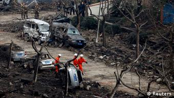 Rescuers search for survivors on a damaged road covered with debris after an explosion in a Sinopec Corp oil pipeline in Huangdao, Qingdao, Shandong Province November 23, 2013. As of Saturday morning, the accident has killed 44 people, with 136 injured, according to Xinhua News Agency. REUTERS/Aly Song (CHINA - Tags: DISASTER ENERGY TRANSPORT TPX IMAGES OF THE DAY)