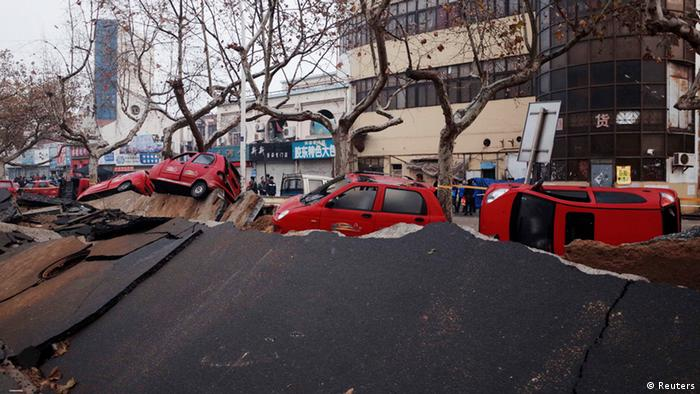 Overturned cars are seen on a damaged street after an explosion at a Sinopec Corp oil pipeline in Huangdao, Qingdao, Shandong Province November 23, 2013. Crude pipelines have been shut-off in the eastern Chinese oil hub of Qingdao pending safety checks a day after a leak triggered a huge explosion that killed 47 people, a refinery official and state media said on Saturday. REUTERS/Mo Yat (CHINA - Tags: DISASTER ENERGY) CHINA OUT. NO COMMERCIAL OR EDITORIAL SALES IN CHINA