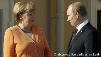 German Chancellor Angela Merkel, in an orange suit, talking to Russian President Vladimir Putin.