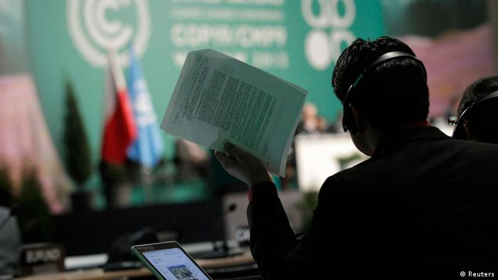 A man holds documents as he listens to statements of delegates during the 19th conference of the United Nations Framework Convention on Climate Change (COP19) in Warsaw November 23, 2013. REUTERS/Kacper Pempel (POLAND - Tags: ENVIRONMENT BUSINESS POLITICS)