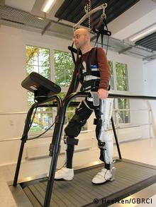 A man walks on a treadmil with the help of a robotic exoskeleton on his legs and torso.