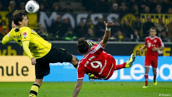 Bayern Munich's Mario Mandzukic (C) tries to score past Borussia Dortmund's Manuel Friedrich (L) during their German first disvison Bundesliga soccer match in Dortmund, November 23, 2013. REUTERS/Ina Fassbender (GERMANY - Tags: SPORT SOCCER) DFL RULES TO LIMIT THE ONLINE USAGE DURING MATCH TIME TO 15 PICTURES PER GAME. IMAGE SEQUENCES TO SIMULATE VIDEO IS NOT ALLOWED AT ANY TIME. FOR FURTHER QUERIES PLEASE CONTACT DFL DIRECTLY AT + 49 69 650050.