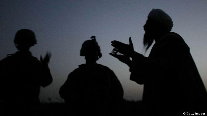 The silhouettes of an interpreter, an Afghan local and an ISAF soldier