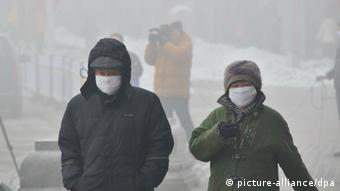 Pedestrians wearing masks walk on a road in heavy smog in Harbin city, northeast China