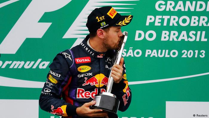 Red Bull Formula One driver Sebastian Vettel of Germany bows as he celebrates winning the Brazilian F1 Grand Prix at the Interlagos circuit in Sao Paulo November 24, 2013. REUTERS/Nacho Doce (BRAZIL - Tags: SPORT MOTORSPORT F1 TPX IMAGES OF THE DAY)