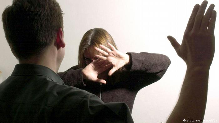 Woman shielding herself against an attack by a man (picture-alliance/dpa)