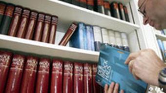 Ein Mitarbeiter der Firma Brockhaus steht mit einem Buch in der Hand an einem Bücherregal im Mannheimer Verlagshaus