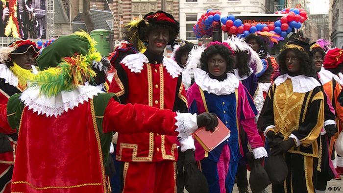 Die bunt kostümierten Zwarte Pieten laufen durch die Straße und verteilen Süßigkeiten an Kinder. (Foto: DW)