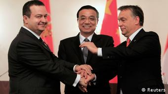 Prime Ministers Ivica Dacic (L) of Serbia and Viktor Orban (R) of Hungary shake hands with China's Premier Li Keqiang after a joint news conference in Bucharest November 25, 2013. REUTERS/Radu Sigheti (ROMANIA - Tags: POLITICS TPX IMAGES OF THE DAY)