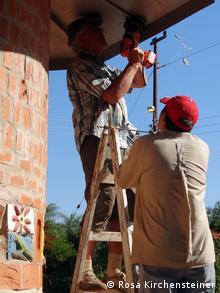 Wilhelm Kirchensteiner (l.) bei der Montage einer Lampe an einem Turmdach mit einem Kursteilnehmer des Solarenergiekurses in Paraguay (Foto: Rosa Kirchensteiner)