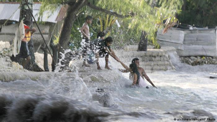 A family living next to the sea in the village of Betio, on the South Pacific island of Kiribati, pull themselves from the high waves of the 'king tide' which hit the fragile atoll, (photo: AP Photo/Jeremy Sutton-Hibbert, Greenpeace, ho)