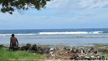 Ein Junge sitzt am Sandstrand auf der Insel Kiribati, am 25.07.2012 neben Abfällen. Hunderte Meter lange Sandstrände, Kokospalmen im Wind, keine Industrie, kaum Autos - auf den ersten Blick erfüllt der schmale Pazifikstaat Kiribati alle Klischees eines Südseeparadieses. Der Schein trügt aber. Die mit Fäkalien verseuchten Strände stinken, Abfall türmt sich überall, Autowracks liegen an der Straße. Foto: Christiane Oelrich/dpa (zu dpa-Reportage: Kampf gegen Klimawandel: Kiribati auf verlorenem Posten vom 16.11.2012)