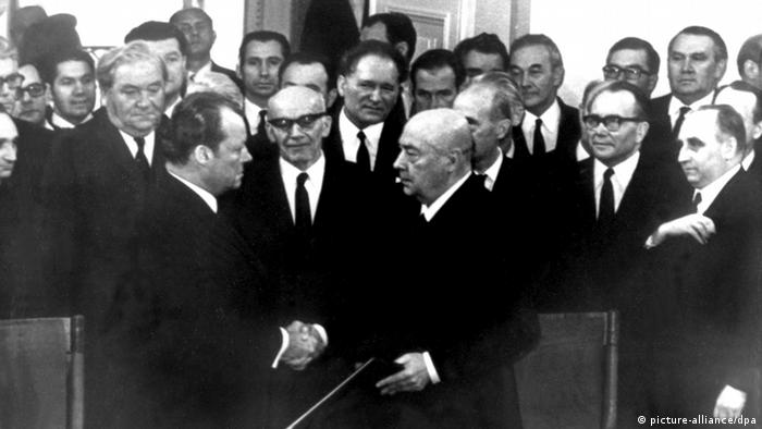 black and white photo of Willy Brandt shaking hands with Polish Prime Minister Josef Cyrankiewicz after the signing, German and Polish politicians looking on