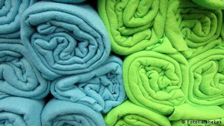 Blue and green fleece blankets rolled up and stacked. (© B747)