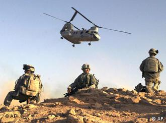 Three US soldiers on the ground, helicopter overhead near Baghdad