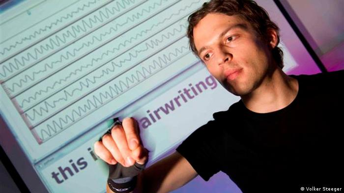 Computer scientist Christoph Amma wears the airwriting glove to write in the air (Photo: Volker Steeger)