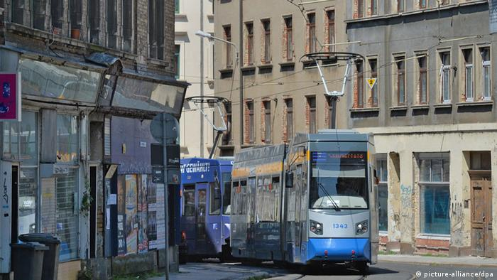 A streetcar drives between dilapidated-looking buildings on Georg-Schwarz-Straße in Leipzig Photo: Hendrik Schmidt/dpa