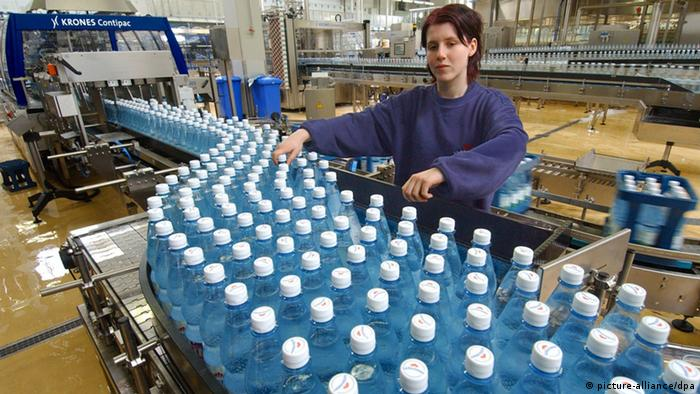 Technician Madlen Fiedler checks bottles as they move on a conveyor belt (Photo: Wolfgang Thieme)