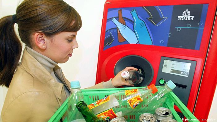 A young woman returns her deposit bottles using a machine
