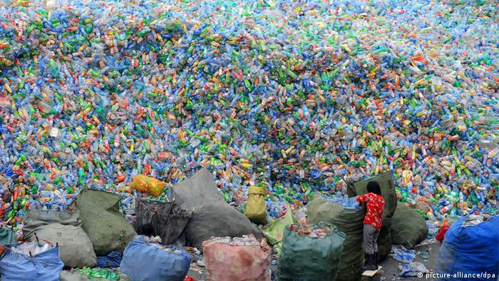 A Chinese worker labors in front of a big pile of waste plastic bottles at a recycling station in Zhengzhou city, central Chinas Henan province, 12 August 2010.