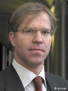 Wearing a dark suit and brown tie, Stefan Schieren looks at the camera in a professional photograph.