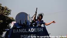 A Bangladeshi policeman gestures from an armoured car after clashes with Bangladesh Nationalist Party (BNP) activists and its Islamist allies during a blockade in Aminbazer, in the outskirts of Dhaka on November 26, 2013. Bangladesh opposition supporters went on the rampage, blocking roads and ripping up railway tracks after rejecting plans for a January 5 election, plunging the nation into fresh political turmoil. AFP PHOTO/ Munir uz ZAMAN (Photo credit should read MUNIR UZ ZAMAN/AFP/Getty Images)