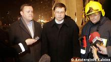 Latvia's Interior Minister Rihards Kozlovskis (L), Prime Minister Valdis Dombrovskis (C) and a senior emergency services official speak to the media near the collapsed c in Riga November 21, 2013. Six people, including two firefighters, were killed and dozens more were feared trapped after the roof of the busy supermarket in Latvia's capital, Riga, collapsed on Thursday evening, a rescue official said. REUTERS/Ints Kalnins (LATVIA - Tags: DISASTER POLITICS BUSINESS MEDIA)