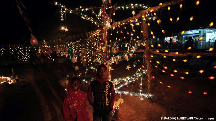 Two children stand in front of Christmas light decorations in Pakistan