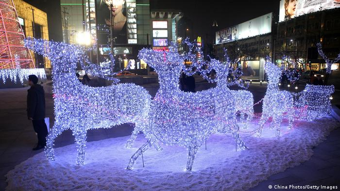 People walk past Christmas light decorations featuring reindeers