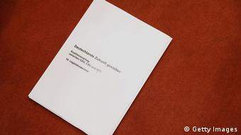 BERLIN, GERMANY - NOVEMBER 27: A copy of the 177-page three-party coalition contract lies on the ground shortly after German Chancellor and Chairwoman of the German Christian Democrats (CDU) Angela Merkel, Chairman of the German Social Democrats (SPD) Sigmar Gabriel and Chairman of the Bavarian Christian Democrats (CSU) Horst Seehofer spoke to the media after signing it at the Bundestag on November 27, 2013 in Berlin, Germany. The three parties worked their way through arduous negotiations on policy issues that concluded with a 17-hour overnight session last night in order to hammer out the final details that will make a new German coalition government possible. The agreement still requires approval by party delegates, which especially in the case of the SPD is uncertain. (Photo by Sean Gallup/Getty Images,)