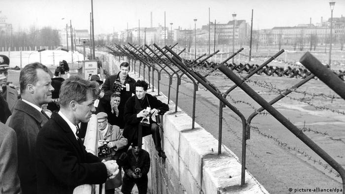 Willy Brandt (lks.) steht mit US-Justizminister Robert Francis Kennedy 1962 an der Mauer (Foto: dpa)