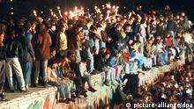 ARCHIV - Jubelnde Menschen sitzen mit Wunderkerzen auf der Berliner Mauer am 11.11.1989. Nach der Öffnung eines Teils der deutsch-deutschen Grenzübergänge in der Nacht vom 9. auf den 10. November 1989 reisten Millionen DDR-Bürger für einen kurzen Besuch in den Westen. In der Folge wurde die innerdeutsche Grenze abgebaut, seit dem 3. Oktober 1990 ist Deutschland wieder vereint. Foto: dpa (zu dpa-Themenpaket vom 27.10.) +++(c) dpa - Bildfunk+++