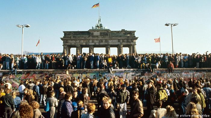Thousands celebrate the falling of the Berlin Wall in a color photograph with the Brandenburg Gate in the background.