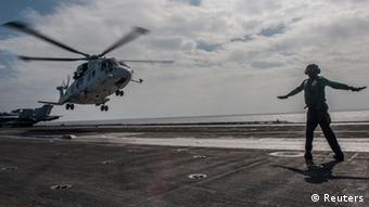 A helicopter of the Japan Maritime Self-Defense Force lifts off from the aircraft carrier USS George Washington during Annual Exercise 2013, at sea in this November 27, 2013 handout provided by the U.S. Navy. The USS George Washington took part in a joint military naval drill with Japan on Thursday in waters off southern Japan, just days after it participated in humanitarian relief operations in the Philippines. More than 20 ships and 7000 U.S. personnel participated in this year's Annual Exercise 2013 which aims at strengthening ties between the United States Navy and the Japan Maritime Self Defence force. While the U.S. Navy would not confirm the exact coordinates, they were able to say the event took place, at one point at least, some 300 kilometers (186 miles) south east of Japan's southern most the islands of Okinawa. This is in the general vicinity, though not within, the new airspace defense zone which China newly established last week. Picture taken November 27, 2013. REUTERS/Mass Communication Specialist Seaman Liam Kennedy/U.S. Navy/Handout via Reuters (MID-SEA - Tags: DISASTER MILITARY POLITICS MARITIME) ATTENTION EDITORS - FOR EDITORIAL USE ONLY. NOT FOR SALE FOR MARKETING OR ADVERTISING CAMPAIGNS. THIS IMAGE HAS BEEN SUPPLIED BY A THIRD PARTY. IT IS DISTRIBUTED, EXACTLY AS RECEIVED BY REUTERS, AS A SERVICE TO CLIENTS