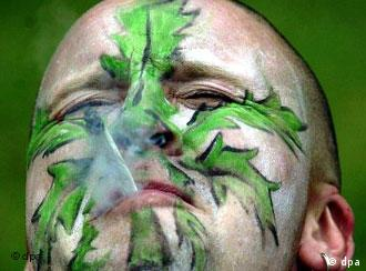 Man smoking with cannabis leaf painted on his face