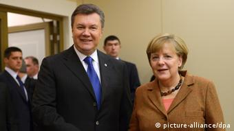 Ukrainian president Viktor Yanukovych with German Chancellor Angela Merkel smiling for the camera at the summit in Vilnius, Lithuania (Photo: Rainer Jensen /dpa)