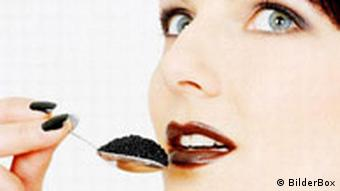 A woman spooning caviar into her mouth