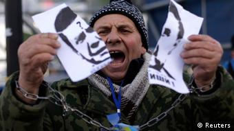 A protester with chained hands tears a portrait of Ukraine's President Viktor Yanukovich during a demonstration in support of EU integration at Independence Square in Kiev November 29, 2013. Ukraine's President Viktor Yanukovich failed on Thursday to salvage an ambitious free-trade pact with the European Union despite a warning that Ukraine was risking its future by turning its back on the deal. Ukraine and the 28-nation EU had aimed to sign an ambitious trade and cooperation agreement at Thursday's summit in the Lithuanian capital Vilnius, which would have marked a historic westwards shift by the former Soviet republic away from Russia's orbit. REUTERS/Stoyan Nenov (UKRAINE - Tags: POLITICS CIVIL UNREST)