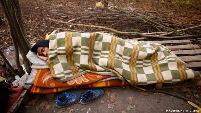 Asylum seeker in forest, under blanket