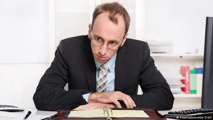 Mann sitzt unzufrieden am Schreibtisch und denkt nach (Fotolia/Jeanette Dietl)