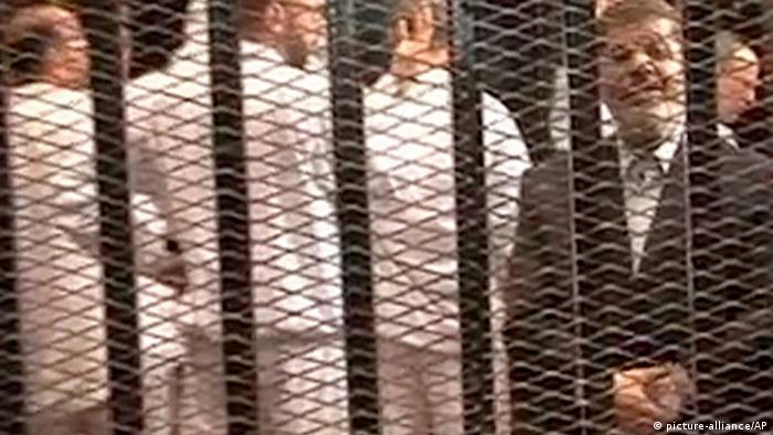 Deposed Egyptian President Mohammed Morsi stands behind bars during his trial in Egypt (c) picture-alliance/AP