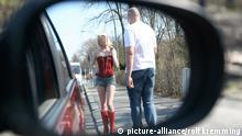 A woman in a red corset is approached by a man on the side of the road (picture-alliance/rolf kremming)
