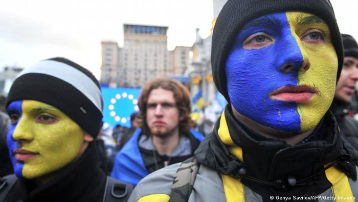 Youths with their face painted with the colors of the Ukrainian flag protest on November 29, 2013 on Independence Square during an opposition protest in Kiev. Ukrainian authorities on November 29 deployed hundreds of riot police to central Kiev where thousands of protesters gathered after President Viktor Yanukovych failed to salvage a key deal with the European Union. Earlier in the day, thousands of Ukrainians locked hands in a symbolic chain linking their ex-Soviet country to the European Union. Protesters formed a human chain that began in the Independence Square and ran along the main Kreshchatyk thoroughfare and other streets. AFP PHOTO/ GENYA SAVILOV (Photo credit should read GENYA SAVILOV/AFP/Getty Images)