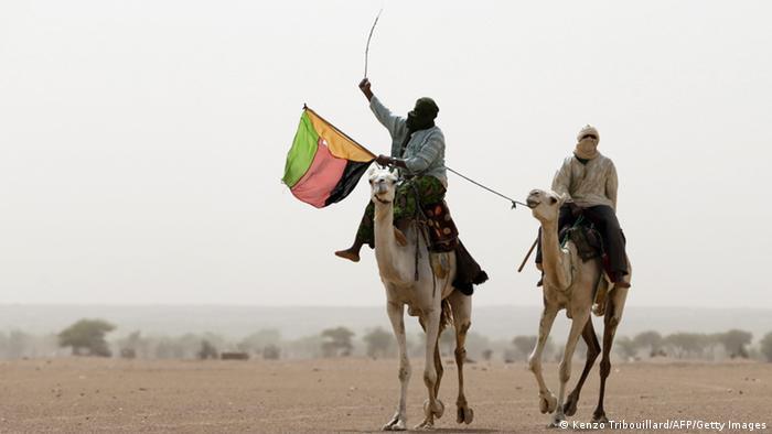 Tuareg auf Kamelen schwenken die Azawad-Fahne Foto: KENZO TRIBOUILLARD/AFP/Getty Images
