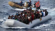 Migrants sit in a boat during a rescue operation by Italian navy off the coast of the south of the Italian island of Sicily in this November 28, 2013 picture provided by the Italian Marina Militare. About 350 migrants, who were travelling in four separate boats were rescued on Thursday in the operation called Mare Nostrum, Italian navy said. Picture taken November 28. REUTERS/Marina Militare/Handout via Reuters (ITALY - Tags: SOCIETY IMMIGRATION MARITIME TPX IMAGES OF THE DAY) ATTENTION EDITORS - THIS IMAGE WAS PROVIDED BY A THIRD PARTY. FOR EDITORIAL USE ONLY. NOT FOR SALE FOR MARKETING OR ADVERTISING CAMPAIGNS. THIS PICTURE IS DISTRIBUTED EXACTLY AS RECEIVED BY REUTERS, AS A SERVICE TO CLIENTS