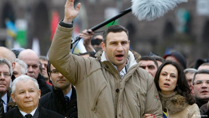 Vitaly Klitschko (C), heavyweight boxing champion and UDAR (Punch) party leader, his wife Natalia (R, first row) and Jaroslaw Kaczynski (L, first row), leader of Poland's main opposition Law and Justice Party (PiS), attend a rally held by supporters of EU integration in Kiev, December 1, 2013. Ukrainian opposition leader Vitaly Klitschko, addressing hundreds of thousands of protesters in central Kiev, called on President Viktor Yanukovich and his government to resign, saying they had stolen Ukraine's dream of European integration. REUTERS/Vasily Fedosenko (UKRAINE - Tags: POLITICS CIVIL UNREST SPORT BOXING)